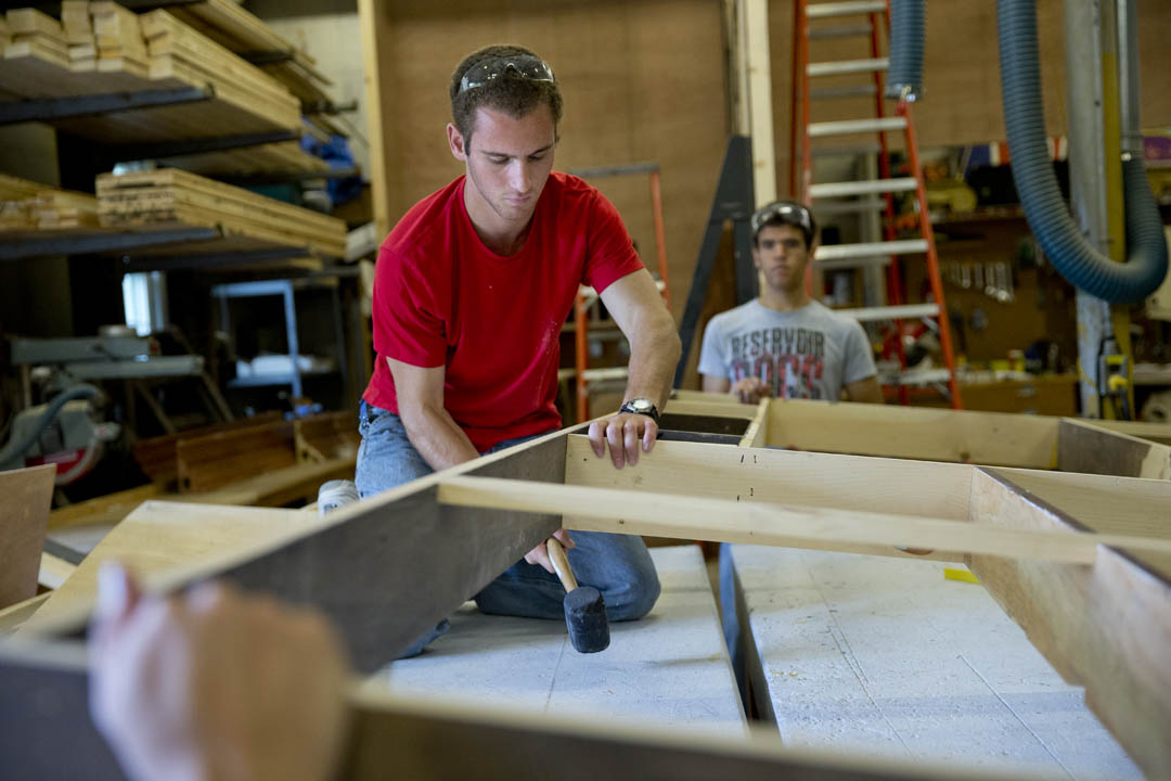 "Daniel Paseltiner '16 of Devon, Pa., works in Pettigrew's theater set construction shop on building a flat for Sara Ruhl's ""In The Next Room,"" directed by Senior Lecturer Kati Vecsey. (Phyllis Graber Jensen/Bates College)"