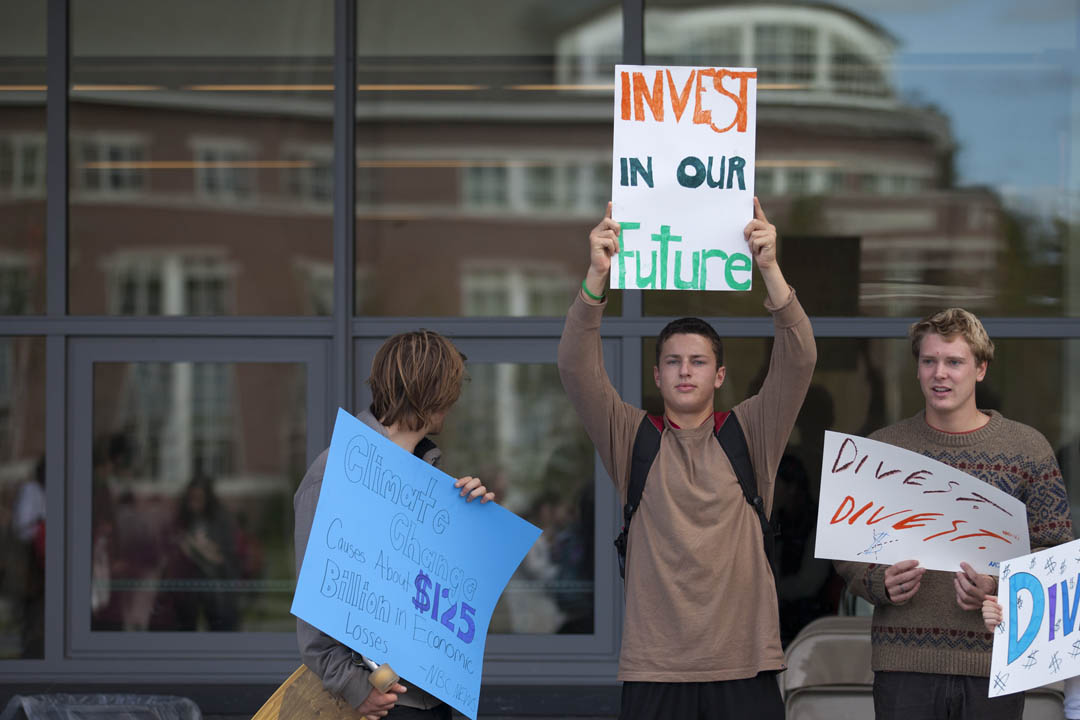 Students hold signs during a BEAM (Bates Energy Action Movement) rally to protest Bates' investments in the fossil fuel industry on Sept. 27, 2013. (Mike Bradley/Bates College)