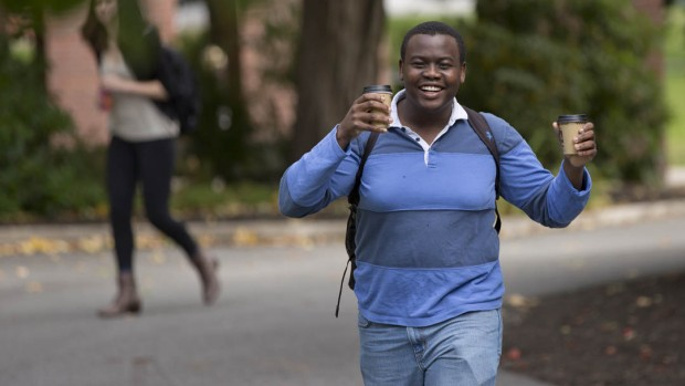 Phillip Dube '16 of Norton, Zimbabwe, carries coffee in one hand and granola in the other in a cross-campus walk.(Phyllis Graber Jensen/Bates College)