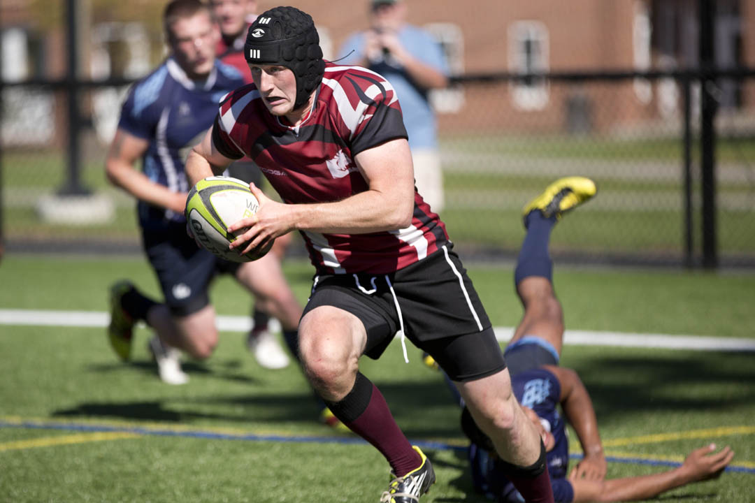 Captain Karl Fisher '14 of Portland moves the ball across Garcelon Field in a men's rugby match against the University of Maine-Orono. (Phyllis Graber Jensen/Bates College)