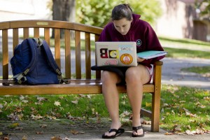 Seated outdoors on the historic Quad, Cat Dioli '14 of Ipswich, Mass., works on a biology paper. (Phyllis Graber Jensen/Bates College)