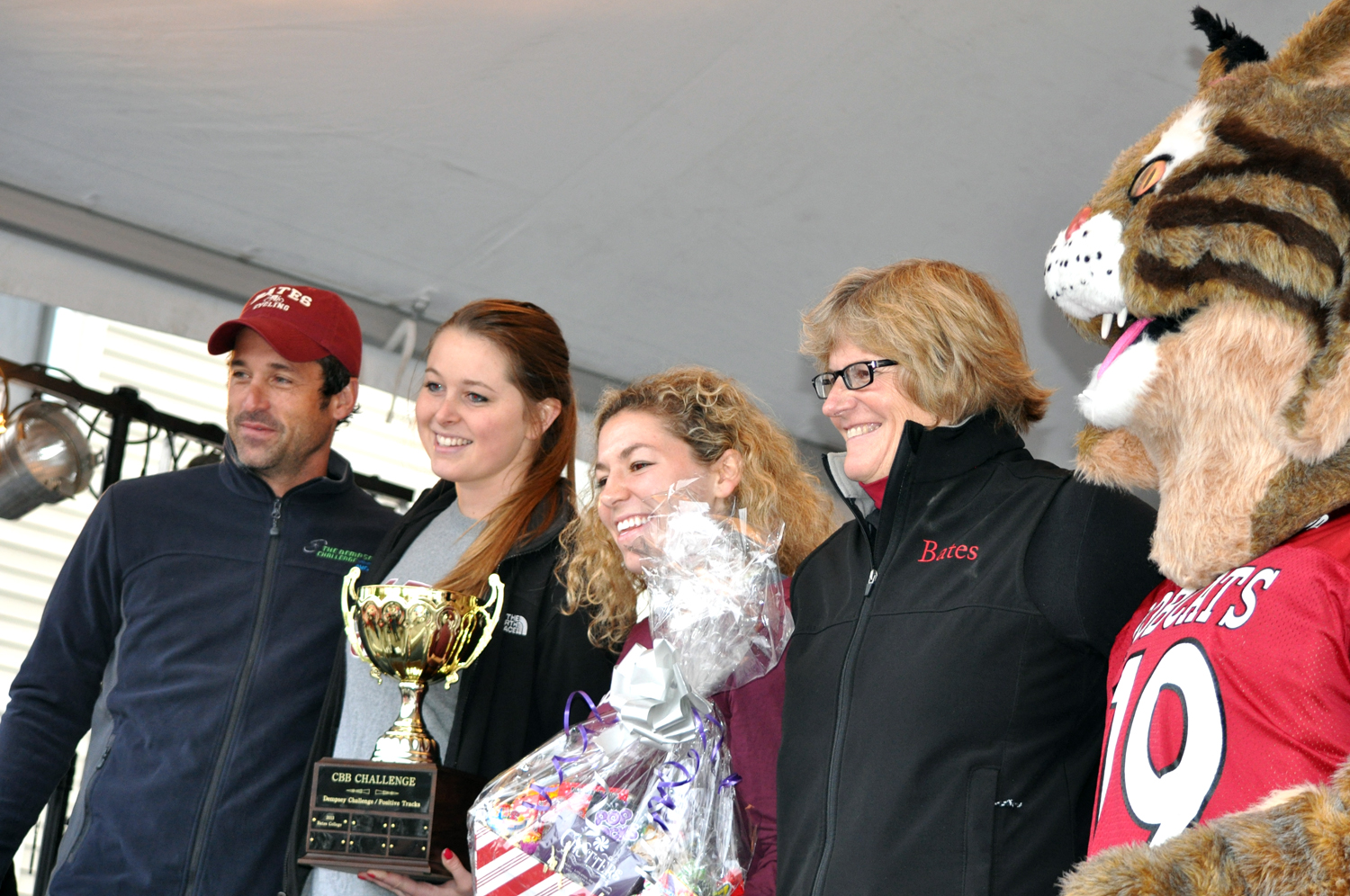 Patrick Dempsey presents the CBB Challenge College Cup to, from left, organizer Hillary Throckmorton '15, Abby Zwetchkenbaum '15 (one of two top Bates fundraisers, along with Julia Gordon '15), President Clayton Spencer and the Bates Bobcat on Oct. 13 during a ceremony in Lewiston's Simard-Payne Park. (Meg Kimmel/Bates College)