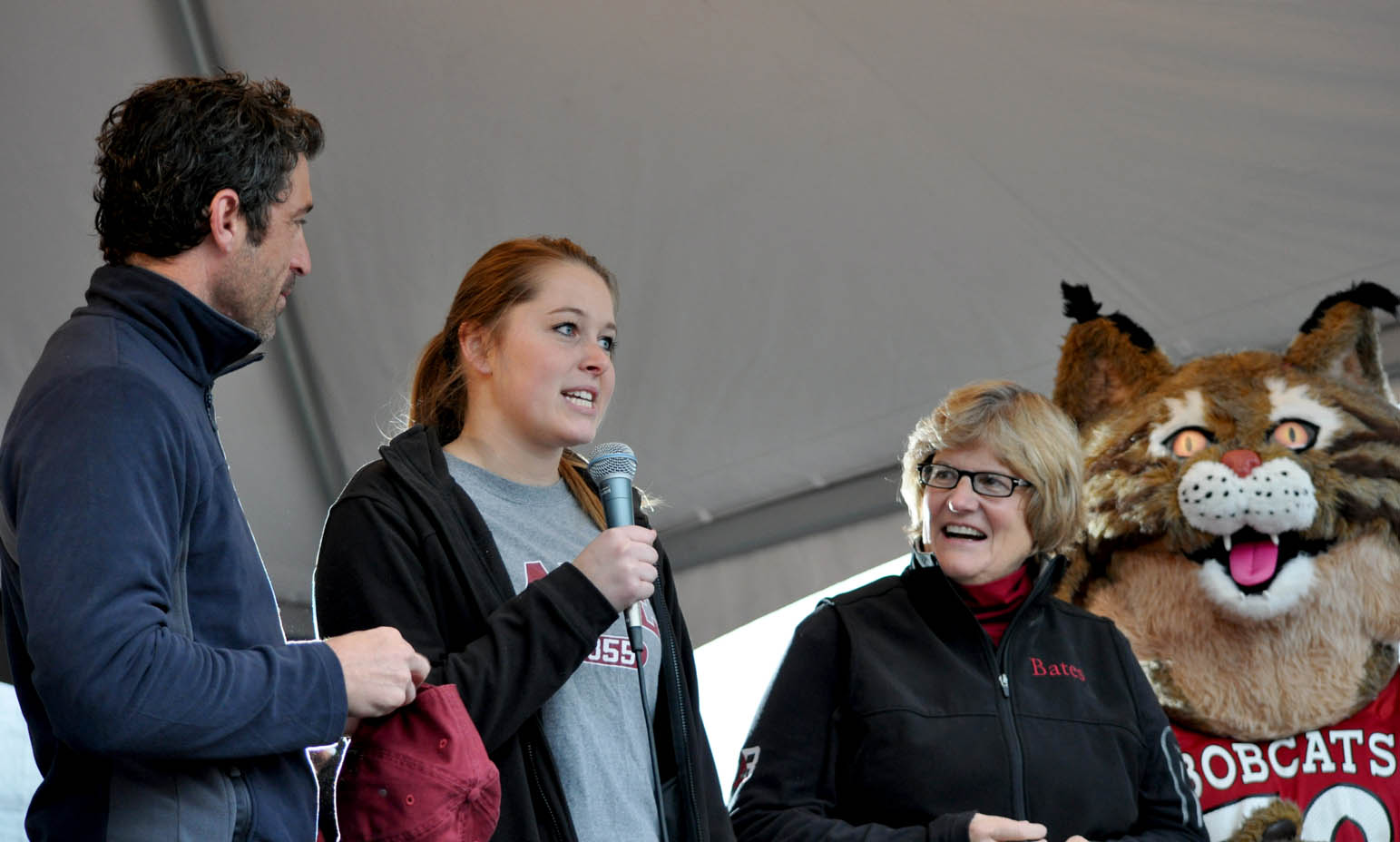 As Patrick Dempsey, President Clayton Spencer and the Bobcat listen,Hillary Throckmorton '15 offers comments after accepting the inaugural CBB Challenge Cup on Oct. 12, 2013. Photo by Meg Kimmel/Bates College.