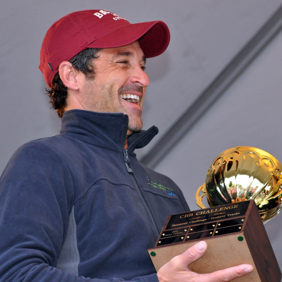 Dempsey laughs while holding the CBB Challenge Cup, inscribed with the first winner: Bates College. (Meg Kimmel/Bates College)