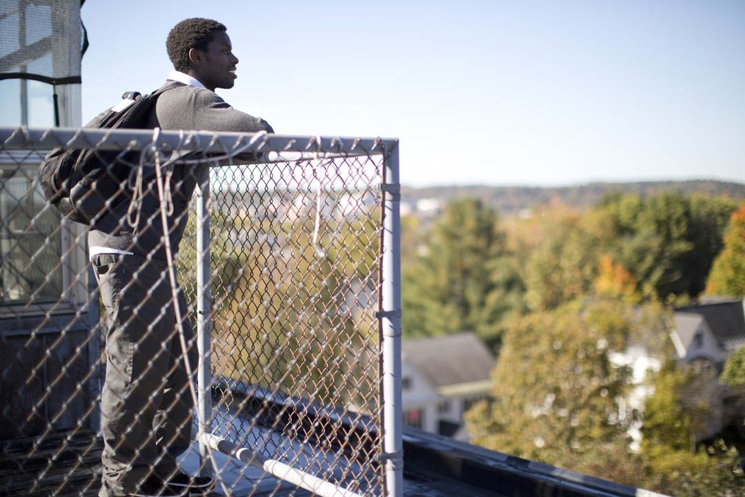 Biochemistry major James Meyo '14 of Nairobi, Kenya, an INBRE grant recipient and Davis United World College Scholar, admiries the view of campus and beyond from the greenhouse exterior on the roof of Carnegie Science. (Phyllis Graber Jensen/Bates College)