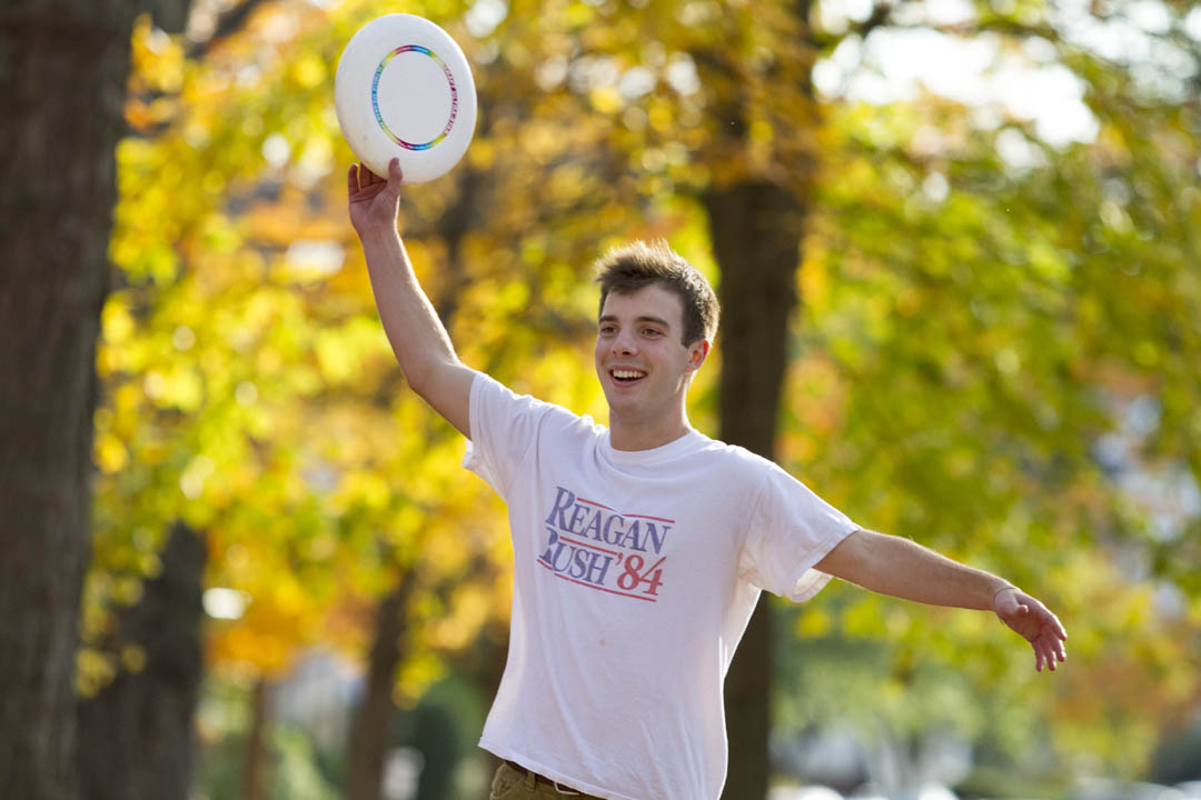Anderson Hershey '17 of Bronxville, N.Y., catches a frisbee on the historic Quad.  (Sarah Crosby/Bates College)
