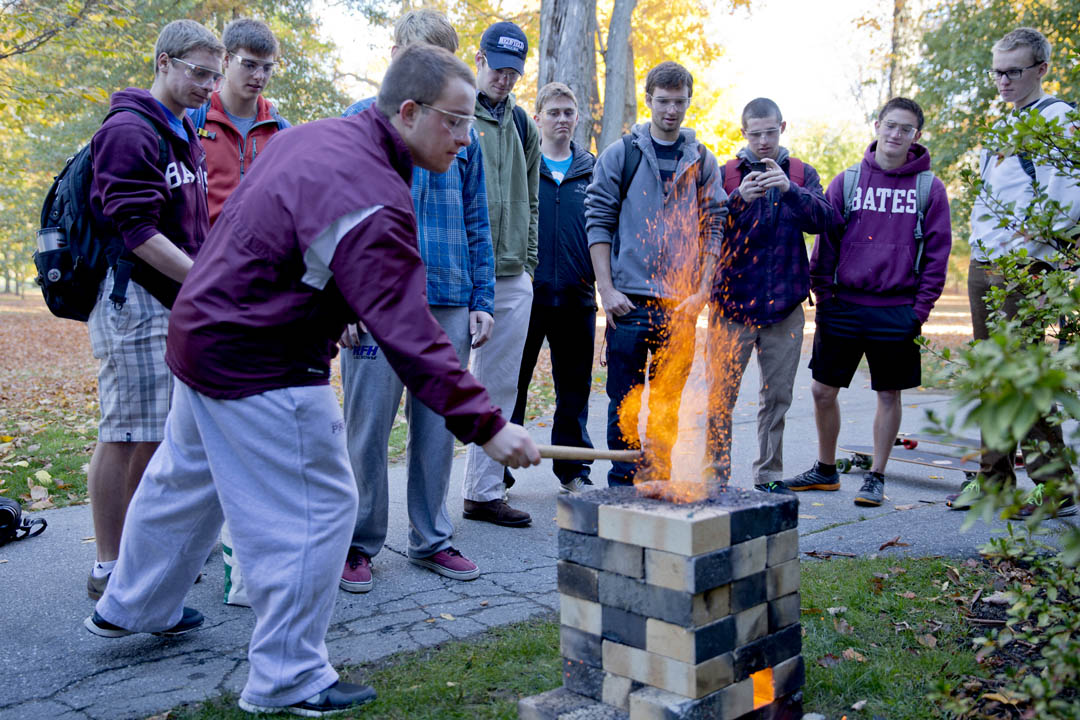 "Students in ""Anatomy of a Few Small Machines,"" a first-year seminar taught by physics lecturer Gene Clough, stoke the fire of a blast furnace outside of Carnegie Science. (Phyllis Graber Jensen/Bates College)"
