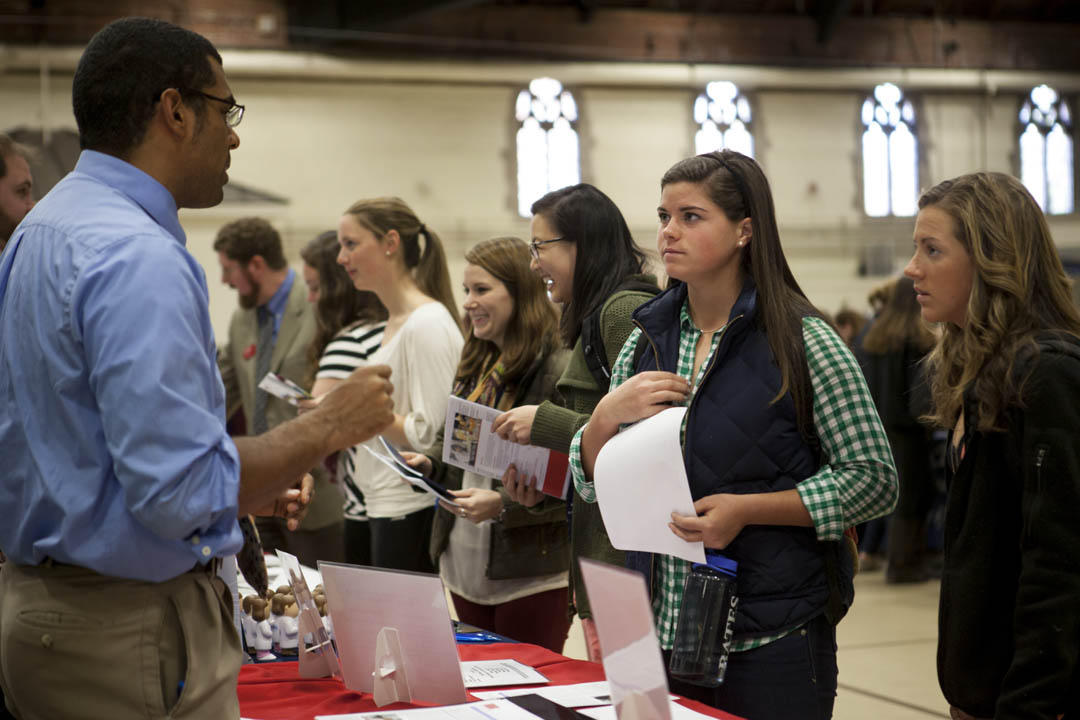 Thomas DeSena of Boston Medical Center speaks with  biology majors Sarah Warden '14 of North Andover, Mass., and Kara Stefaniak '14 of Needham, Mass., at a graduate school fair in the Grey Cage. Both women are investigating Boston University School of Medicine for mental health and behavioral medicine programs. (Sarah Crosby/Bates College)