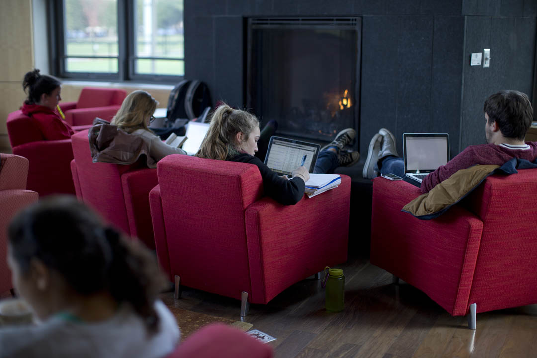 Students enjoy the comfort and warmth of a roaring fire on a crisp fall day while studying in the Fireplace Lounge of New Commons. (Phyllis Graber Jensen/Bates College)