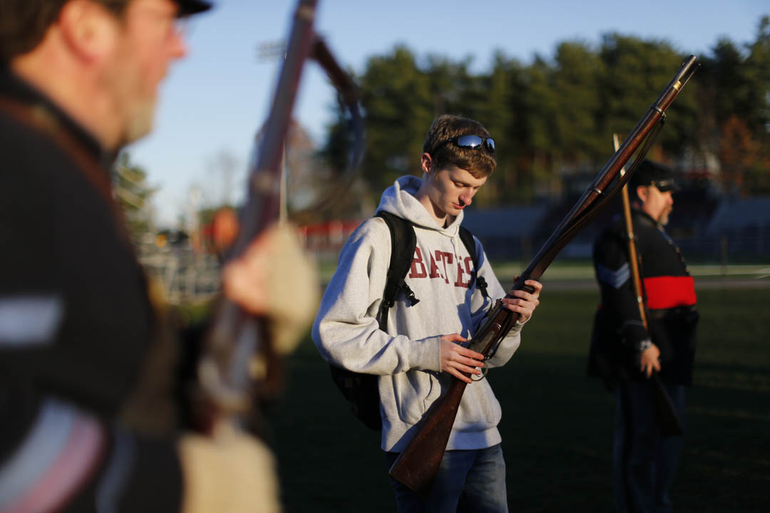 "Ben Brimelow '16 of Greenwich, Conn., a student in AC/HI 141 ""America in the Age of the Civil War,"" taught by Professor of History Margaret Creighton, checks an historical firearm between Garcelon Field and Pettengill Hall with the Third Maine Regiment. (Phyllis Graber Jensen/Bates College)"