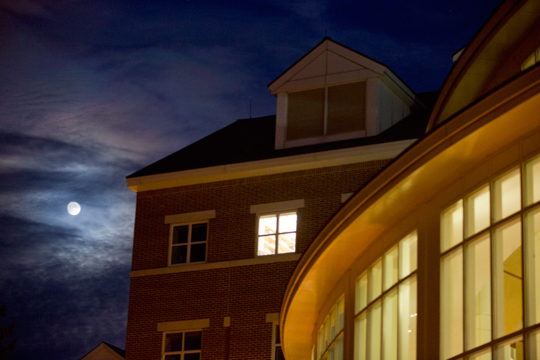 A full moon sits next to Pettengill Hall. (Phyllis Graber Jensen/Bates College)