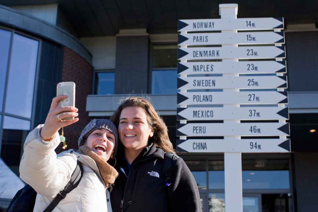 Suraya Atallah '15 of Beirut, Lebanon (right), poses for a selfie with Sara El Assaad '14 of Aix en Provence, France, in front of a signpost of some Maine towns that are named after foreign countries and cities. The sign appears in front of New Commons the day of the annual Harvest Dinner.(Phyllis Graber Jensen/Bates College)