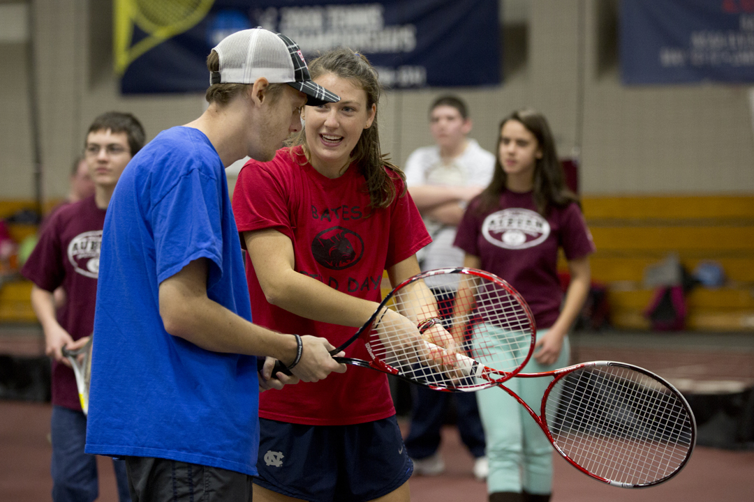 Varsity tennis player Lucy Brennan '15 of Freeport, Maine, and teammates offer a clinic for intellectually disabled athletes in Merrill Gym, part of the college's  partnership with Special Olympics. (Phyllis Graber Jensen/Bates College)