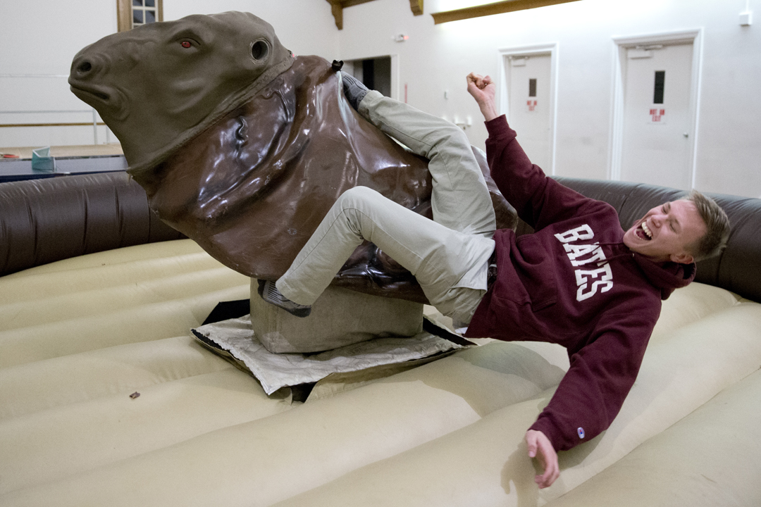 Nick Luther '16 of Concord, Mass., rides a mechanical bull during the Student Activities Study Break in Chase Hall. (Phyllis Graber Jensen/Bates College)