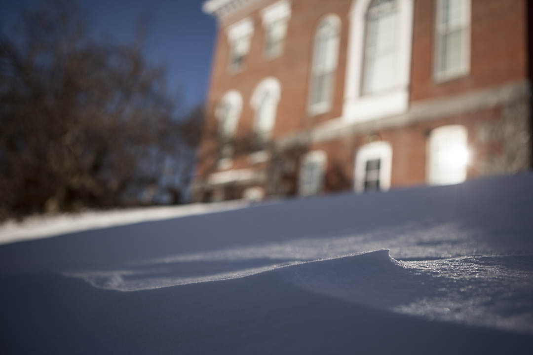 Snow drifts in front of a sunlit Hathorn Hall. (Sarah Crosby/Bates College)