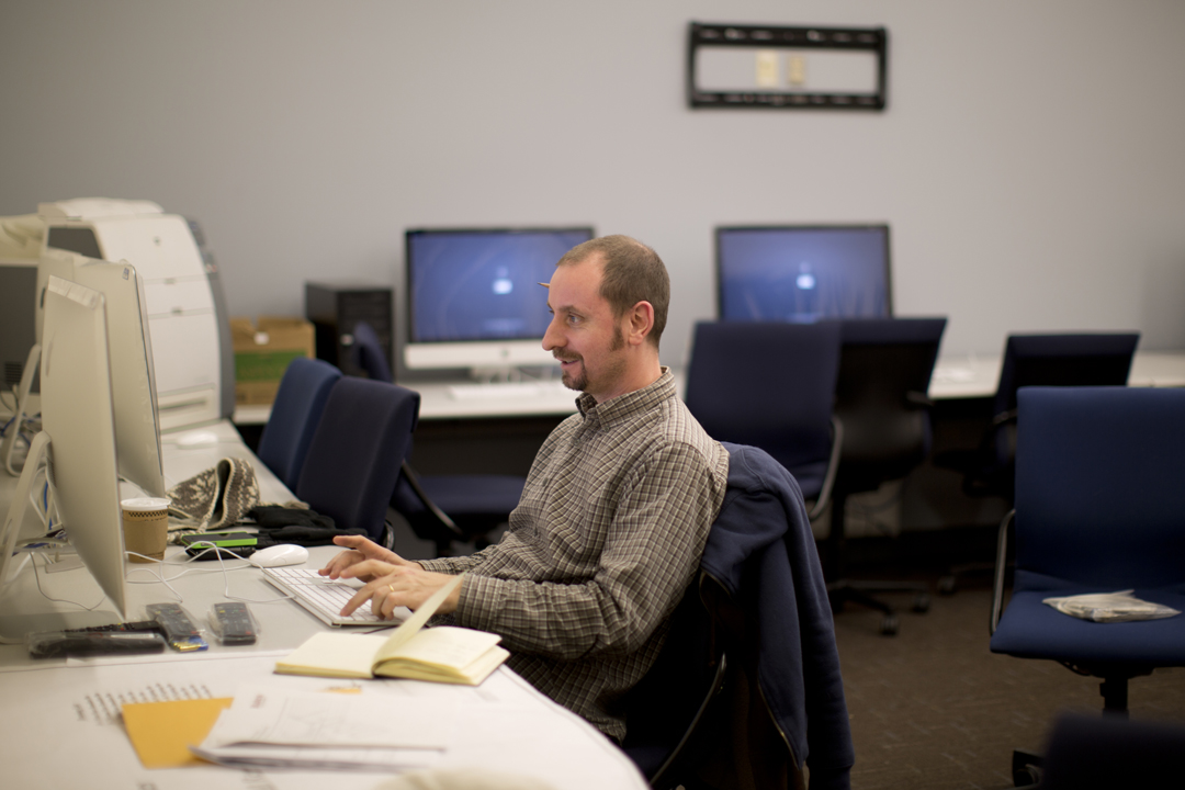 Paul Benham, who handles Mac computer installations, among other duties, puts the finishing touches on a new iMac lab in Pettigrew Hall. (Phyllis Graber Jensen/Bates College)