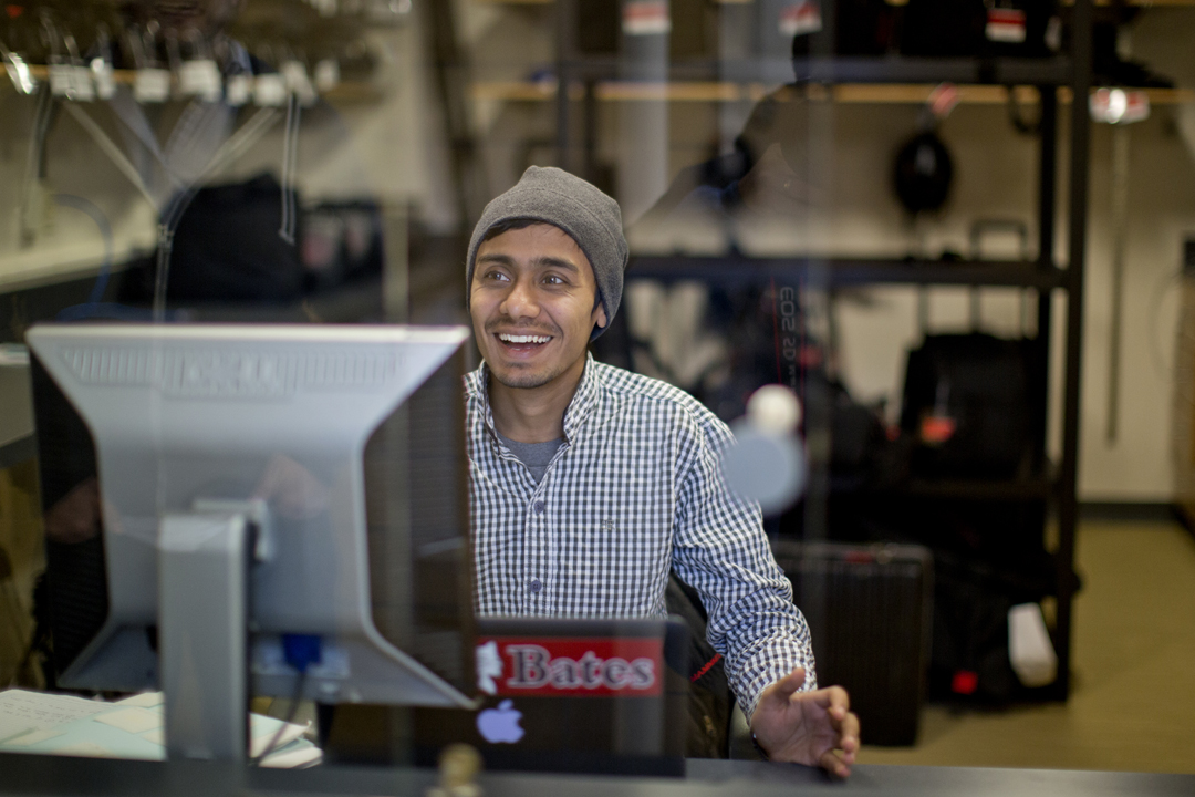 Chemistry major Adnan Shah '15 of Kathmandu, Nepal works his campus job helping people borrow computers and multimedia gear. (Phyllis Graber Jensen/Bates College)