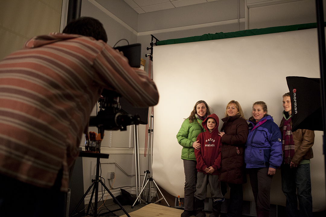 "Logan Greenblatt '14 of the Imaging Center photographs, from left,  Assistant Director of Operations and Analysis Sheila Anderson and her family, in the ""Giant Photo Booth."" (Sarah Crosby/Bates College)"