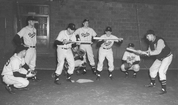 Head coach Chick Leahey '52 demonstrates bunting technique during a practice in Gray Athletic Building in the 1950s. (Muskie Archives and Special Colleciton Library)