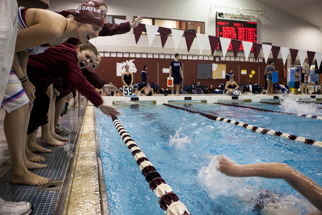 From left, Lyndsay Wallace '14 and Gabrielle Sergi '14 offer encouragement as Bates swimming and diving competes against Middlebury at Tarbell Pool. (Sarah Crosby/Bates College)
