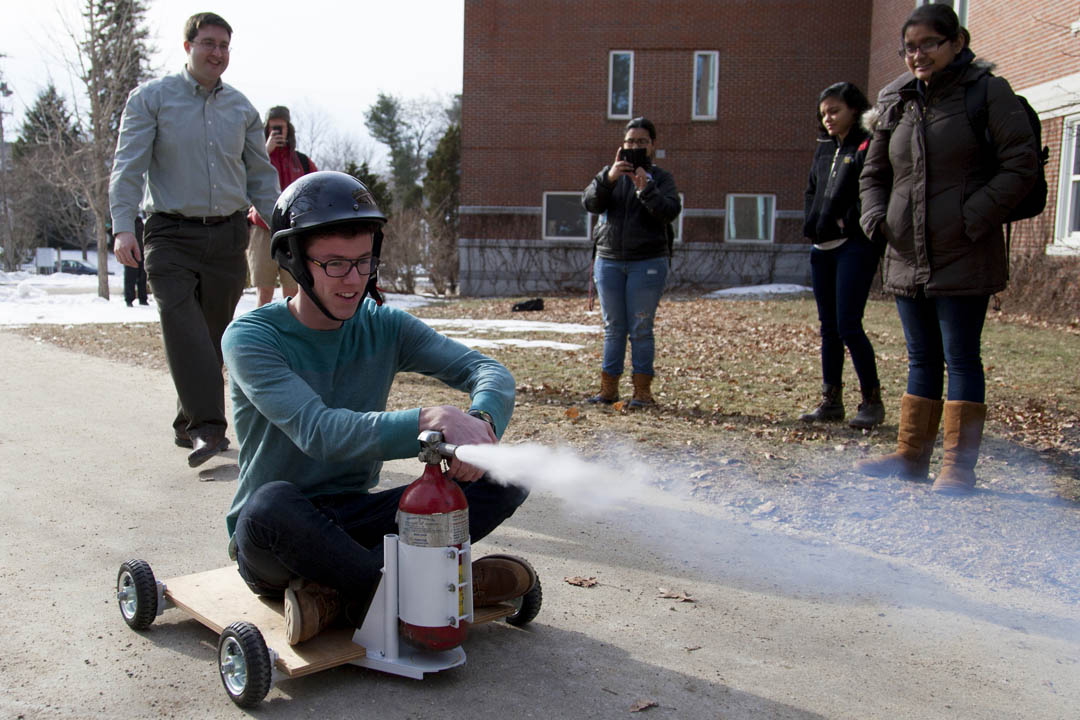 Ben Palmer '16 rides a wheeled cart propelled by a tank of CO2 in a demonstration of momentum conservation run by Michael Durst (left), visiting assistant professor of physics, in his Newtonian mechanics course. (Marc Glass '88/Bates College)