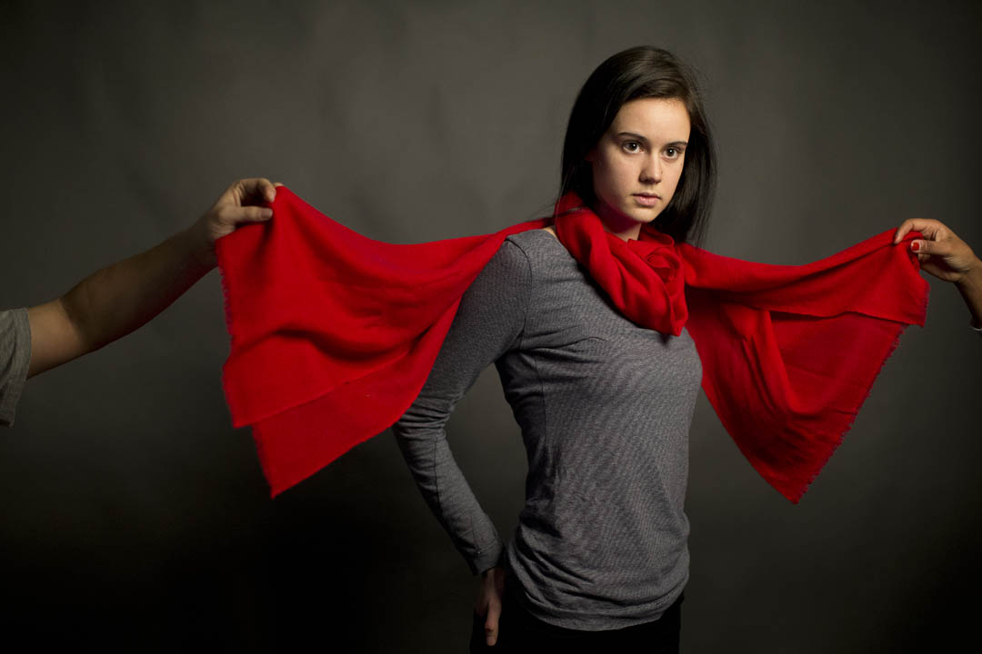 During a photography shoot in the Coram Imaging and Computing Center's photo studio, Margaret Pope '16 models a scarf made for Bates by an ethical fashion company, Himalayan Spirit, in Nepal. Suraj Karmacharya '14 is the firm's marketing director. (Phyllis Graber Jensen/Bates College)