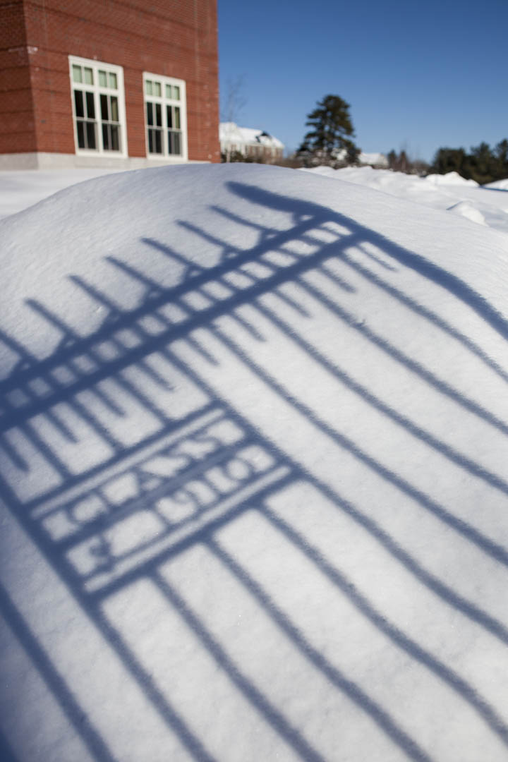 A shadow of the Class of 1910 gate falls outside of Roger Williams Hall. (Sarah Crosby/Bates College)