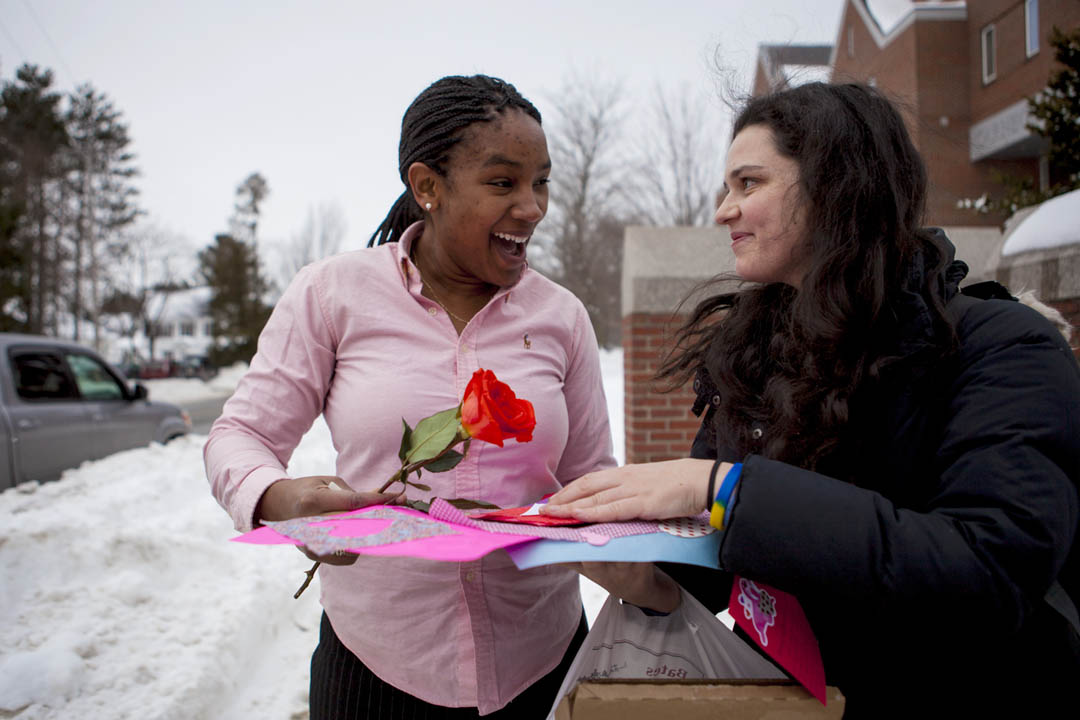 Simone Schriger '14 (right) surprises Cheri-Ann Parris '13 with flowers and a handmade valentine. (Sarah Crosby/Bates College)
