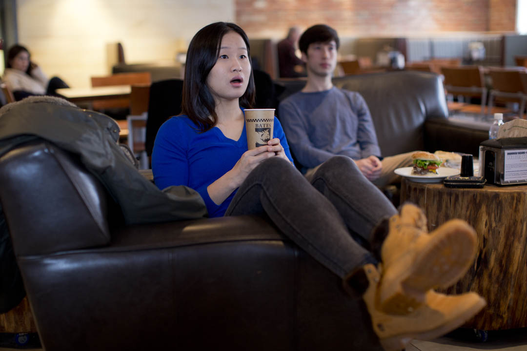 """""""Growing up, I used to watch figure skating while having dinner with my family,"""" says economics and math double major Lei Lei '14 of Nanjing, China, watching Olympic women's figure skating while eating brunch in the Den with Rohan Jaffrey '14 of Jersey City, N.J. (Phyllis Graber Jensen/Bates College)"""