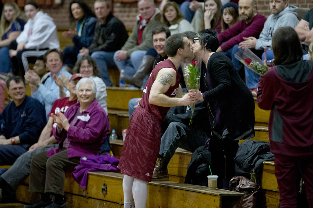 With a bouquet and a kiss, Luke Matarazzo '14 of Shelton, Conn., greets his mother courtside in Alumni Gym prior to his final game for Bates. (Phyllis Graber Jensen/Bates College)