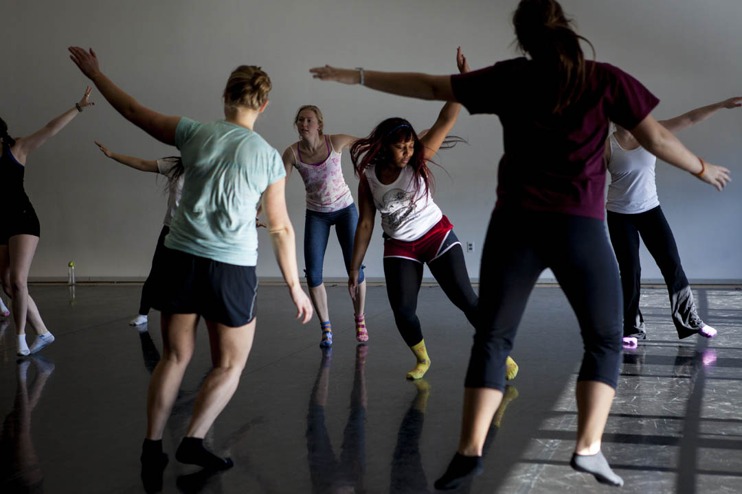 Brittney Davis '14, center, dances with Bates modern dancers and Lewiston folk dancers during a contradance rehearsal in the Marcy Plavin Studios. The dance is a collaboration between the two groups and fuses traditional French-Canadian contradance and modern jazz. (Sarah Crosby/Bates College)