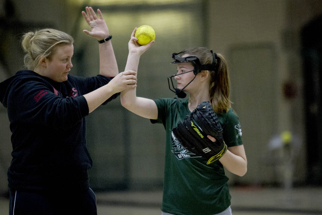 Bates softball coach McKell Barnes offers tips on technique to Hope Hutchinson, 12, of Greene during a youth clinic with the softball team in Gray Cage. (Sarah Crosby/Bates College)