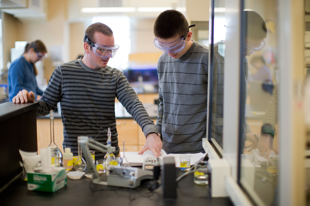 """Visiting Assistant Professor of Chemistry Ryan Nelson, left, assists a student in a  lab for CH/ES 108B, """"Chemical Reactivity in Environmental Systems."""" (Phyllis Graber Jensenj/Bates College)"""