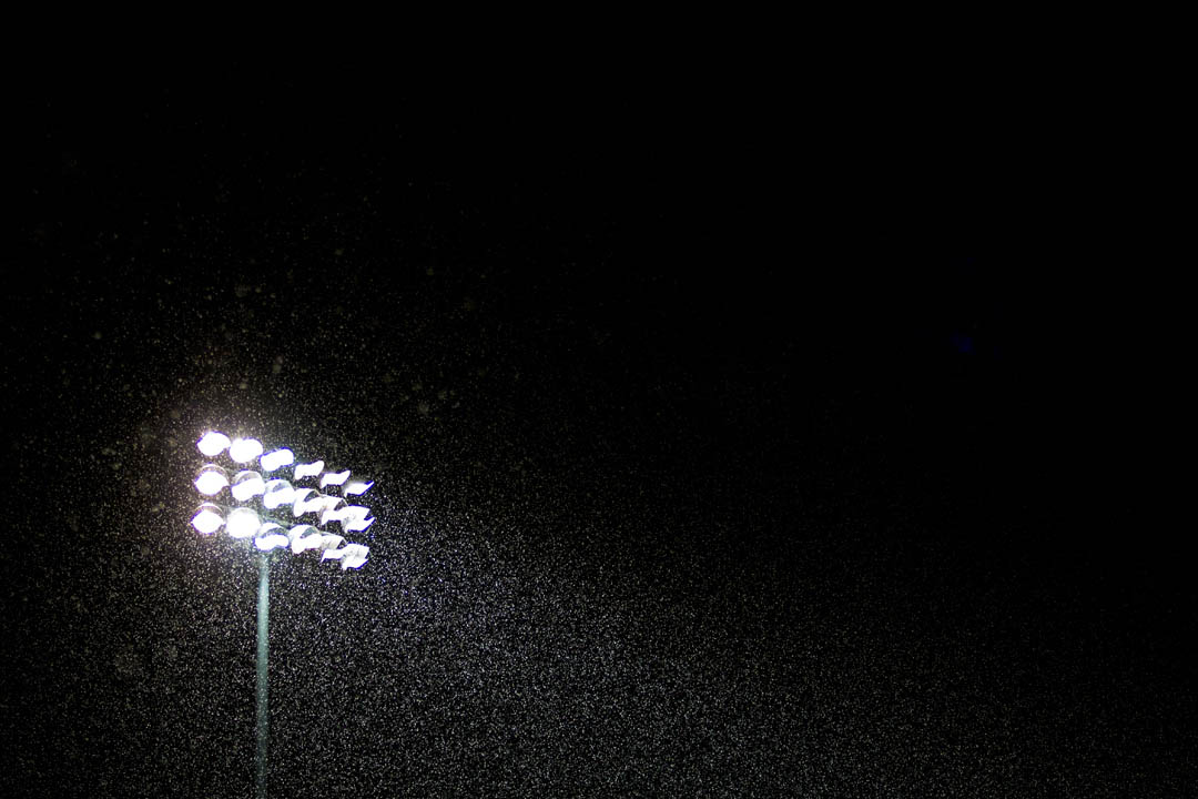Light snow arrives on Garcelon Field during the men's  lacrosse game vs. Husson University. (Sarah Crosby/Bates College)