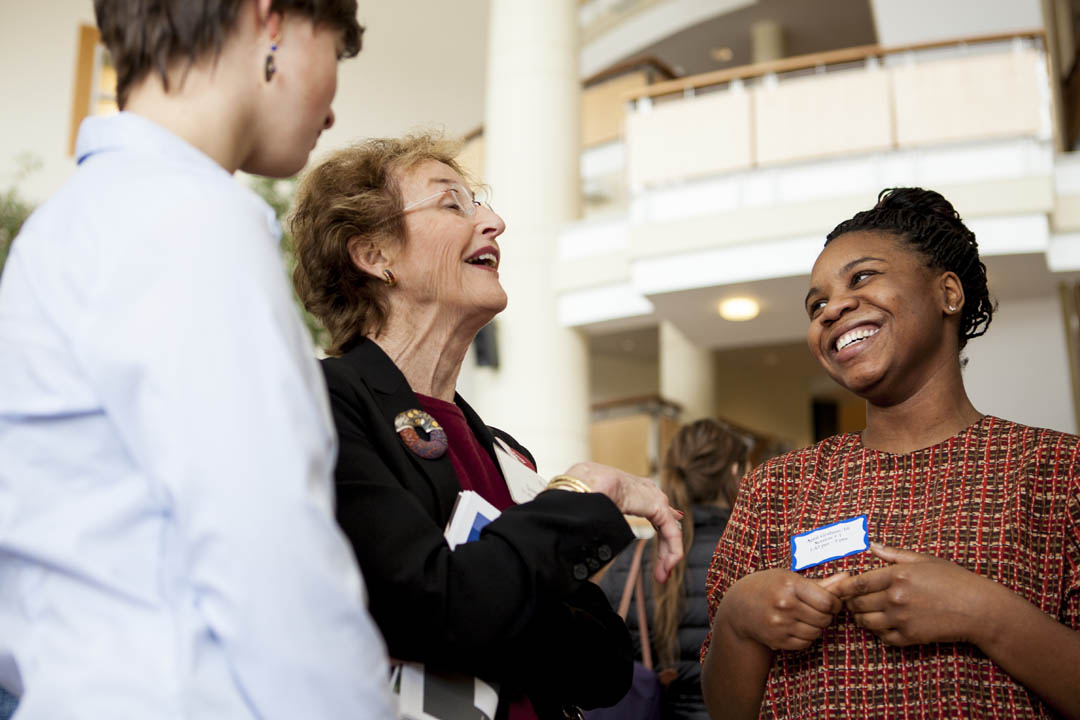 "From left, Bridget Ruff '18, Jane Wellehan '60 and April Graham '16 enjoy a moment during Graham's poster presentation, ""Women's Grassroots Organization in Africa."" (Sarah Crosby/Bates College)"