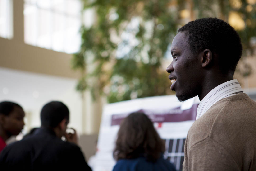 "Emmanuel Toroitich '15 surveys the crowd while participating in a poster session. His study focused on ""Urban Lead Pollution in Lewiston."" (Sarah Crosby/Bates College)"
