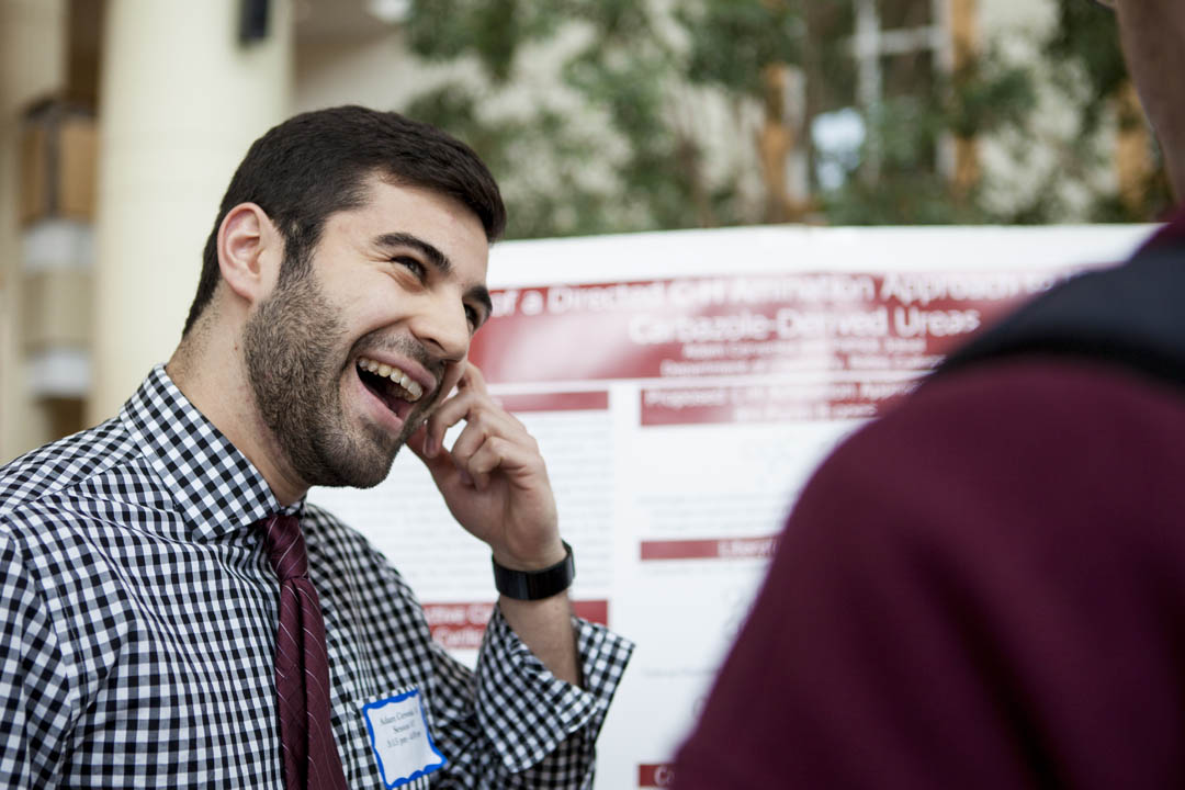 "Adam Cervenka '14 reacts during a conversation about his poster, ""Application of a Directed C-H Activation Approach to the Synthesis of Carbazole-Dervied Ureas."" (Sarah Crosby/Bates College)"