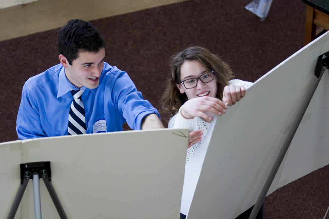 Michael Martin '14 and Jane Mayer' 14 hang their posters for presentation. (Sarah Crosby/Bates College)