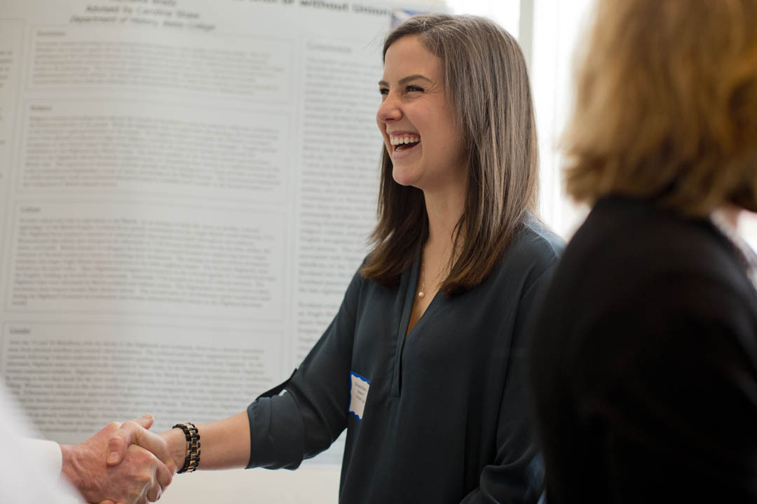 Michaela Brady '14 ends her presentation on Scottish independence, with or without union, with a handshake during the first poster session. (Phyllis Graber Jensen/Bates College)