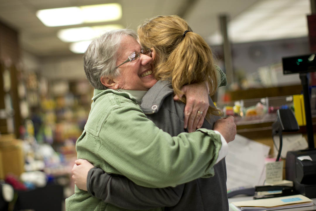 Bookstore director Sarah Potter '77 hugs Hallie Balcomb '14 of Gorham, a mathematics major who works in the store. (Phyllis Graber Jensen/Bates College)