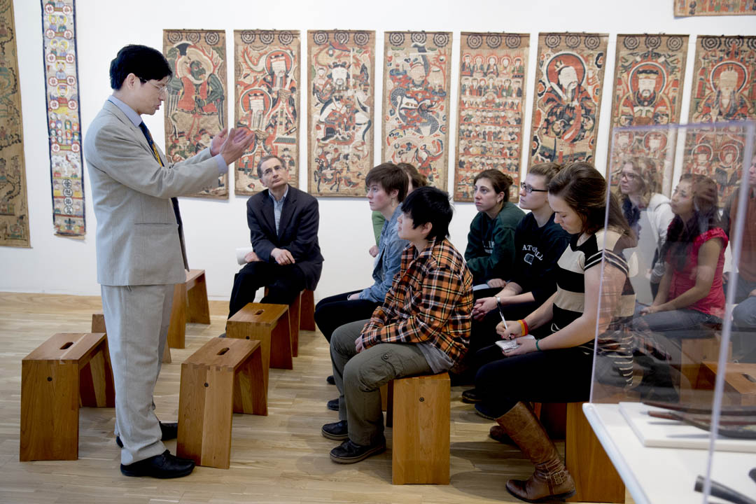 "As part of their analysis of music and religion, students of James Parakilas (seated) listen to a museum gallery talk on ""The Art of the Shaman in Vietnam and Southern China"" by Professor of Art and Visual Culture Trian Nguyen. Parakilas is the college's Moody Family Professor of Performing Arts. (Phyllis Graber Jensen/Bates College)"