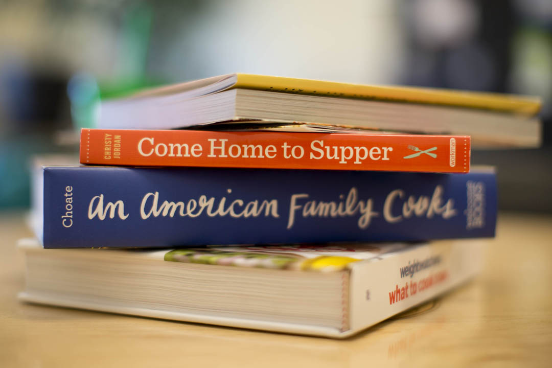 Newly arrived cookbooks sit on a table in the office of Christine Schwartz, the college's assistant vice president for dining, conferences and campus events. (Phyllis Graber Jensen/Bates College)