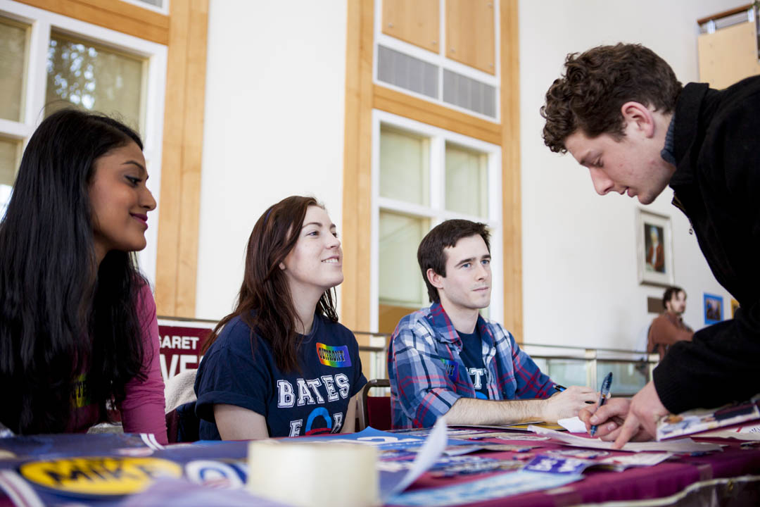 Maitri Chittidi '17 of Nashua, N.H., Carly Peruccio '16 of Manchester, Conn., and Teddy Rube '16 of Manlius, N.Y., share information about the Bates Democrats with prospective student Dylan Thombs of Monmouth, Maine, during an activities fair for newly admitted students in Pettengill Hall's Perry Atrium. (Sarah Crosby/Bates College)