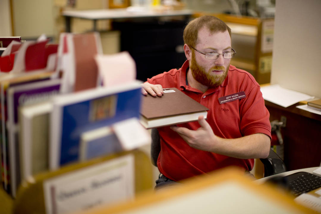 """That's the point of libraries. We don't have secrets,"" says Jeff Kazin '04, a library assistant for public services, explaining how he approaches his job at the front desk of Ladd Library. (Phyllis Graber Jensen/Bates College)"