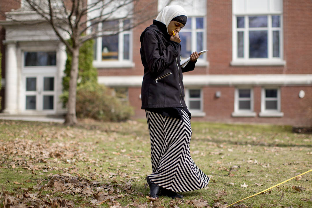 Biology major Asha Mohamud '15 of Lewiston learns field data-collection techniques on the Historic Quad. She's in a course examining the patterns and history of New England forests and plant communities, taught by plant ecologist Lea Johnson. (Phyllis Graber Jensen/Bates College)