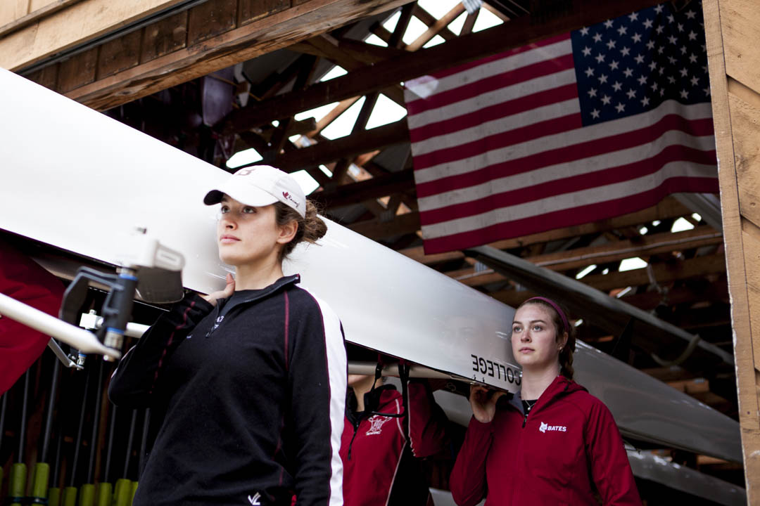 Rowers walk their shells from the Bates boathouse prior to the President's Cup Regatta on the Androscoggin River. The boathouse is a few minutes from campus in Greene. (Sarah Crosby/Bates College)