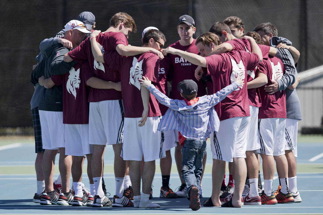 Men's tennis players welcome a youngster to their huddle before a match vs. Amherst. The boy is an honorary Bobcat through  Team IMPACT, a nonprofit that seeks to deliver better quality of life to ill children through sports. (Phyllis Graber Jensen/Bates College)