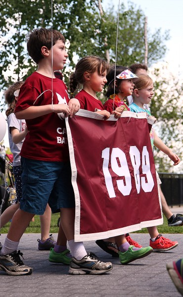 Children of Class of 1989 alumni carry the class banner during the Alumni Parade on June 7. (Jay Burns/Bates College)