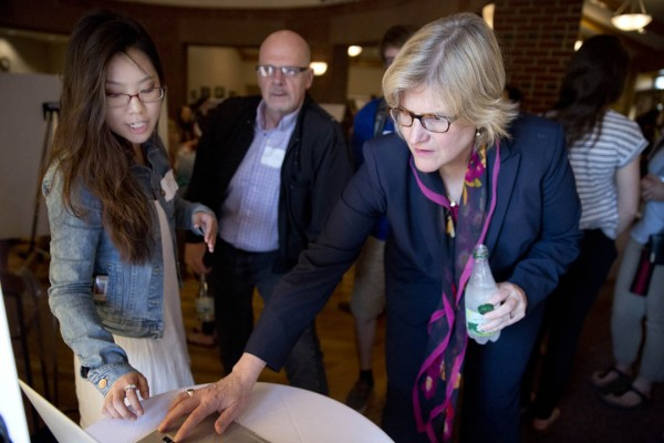 Hyo Sun Hong '16 of Montclair, Calif., who studied graphic design during Short Term under Brandy Gibbs-Riley '96, explains to President Spencer and Professor of Russian Dennis Browne how she and her classmates developed a logo for the annual Harvest Dinner. (Phyllis Graber Jensen/Bates College)