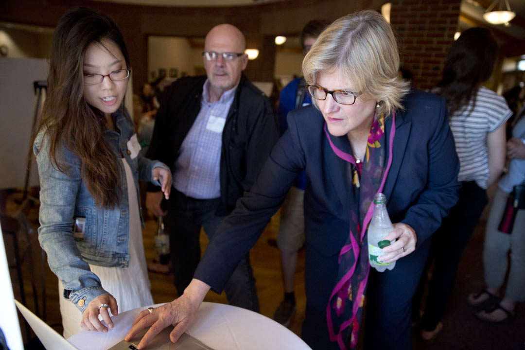 Hyo Sun Hong '16 of Montclair, Calif., explains a graphic design project to President Clayton Spencer and Professor of Russian Dennis Browne during an event showcasing student work in Short Term. (Phyllis Graber Jensen/Bates College)